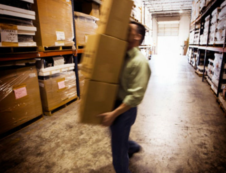 Man is moving three boxes goods in warehouse