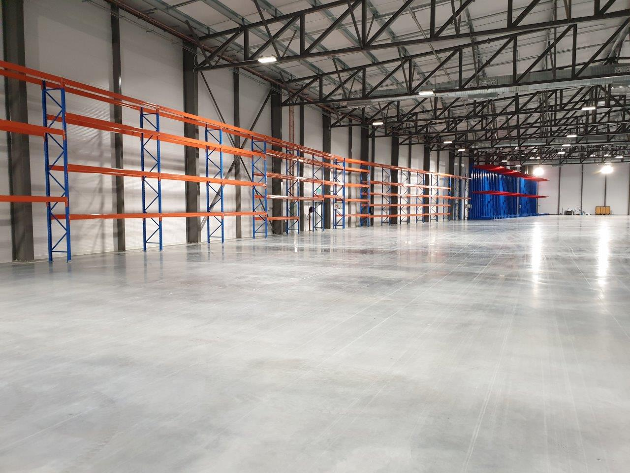 empty warehouse with several blue and orange goods shelf